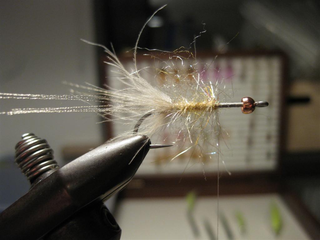 Unter erneuter Zuhilfenahme der Split-Thread-Technik wird ein fluffiger Dubbingstrang erstellt, welcher um den Hakenschenkel bis 2/3 der Hakenlänge gebunden wird. Ein Stück Klettverschluß hilft die Grannen des Dubbing aus dem Strang heraus zu zupfen.